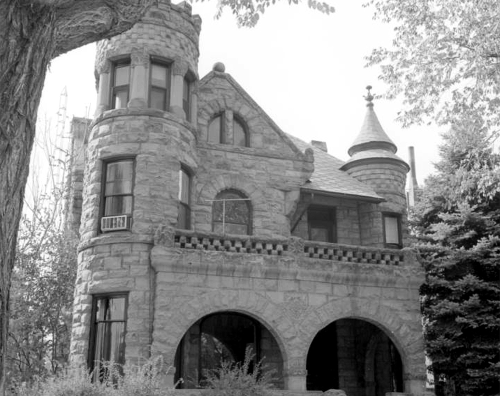 "Exterior view of ""Gargoyle"" House, 302 West Pitkin Avenue, Pueblo, Colorado, shows a two-story rock-faced stone residence with corner tower, turret, balustrade, and semi-elliptical double-arched porch. Between 1960 and 1980. (Sandra Dallas/Denver Public Library/Western History Collection/X-10783)  history colorado; historic; denver public library; dpl; archive; archival; denverite"