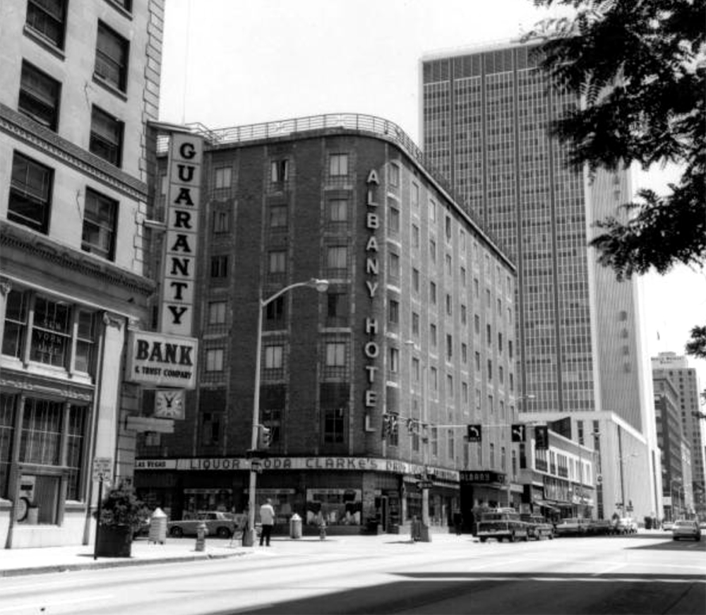 """View of 17th (Seventeenth) Street in downtown Denver, Colorado. Shows the Guaranty Bank and Trust Company, the Albany Hotel, the Colorado National Bank building, and the Brown Palace Hotel. Signs read: """"Las Vegas. Liquor. Soda. Clarke's Drug."""" Circa 1965. (Sandra Dallas/Denver Public Library/Western History Collection/X-29193)  history colorado; historic; denver public library; dpl; archive; archival; denverite"""
