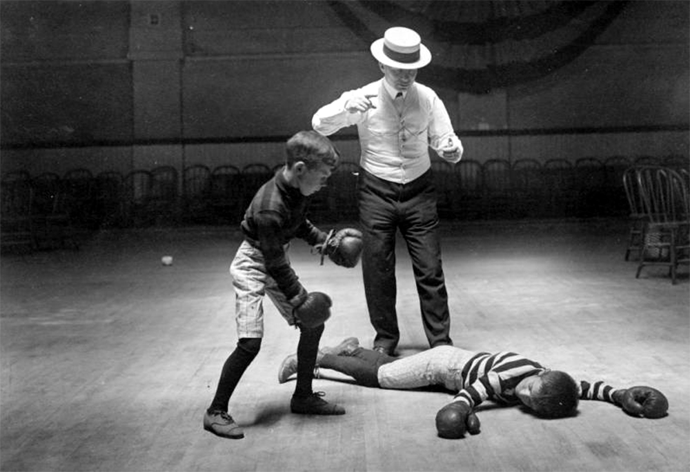 Two boys fight with boxing gloves, a man with a pocket watch acts as referee, probably in Denver, Colorado. Between 1910 and 1920. (Harry Mellon Rhoads/Denver Public Library/Western History Collection/Rh-5870)  historic; denver public library; dpl; archive; archival; denverite