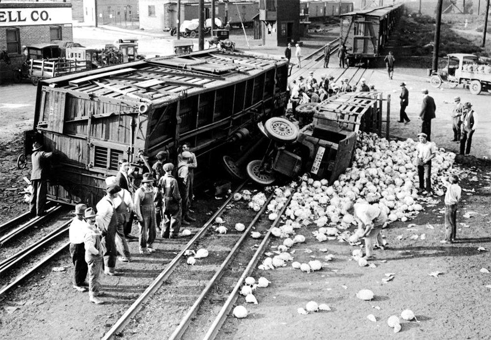 """A relatively harmless cabbage accident some years back."" A crowd of people are gathered around a spilled truckload of cabbage and a derailed railroad train car in Denver, Colorado. Between 1920 and 1930. (Harry Mellon Rhoads/Denver Public Library/Western History Collection/Rh-5916)  historic; denver public library; dpl; archive; archival; denverite"