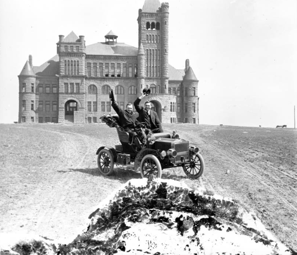 Harry M. Rhoads, behind the steering wheel, poses in a convertible with passenger in front of Westminster University or College, at 3455 West 83rd Avenue in Westminster (Adams County), Colorado.  Circa 1895. (Harry Mellon Rhoads/Denver Public Library/Western History Collection/Rh-967)  historic; denver public library; dpl; archive; archival; denverite
