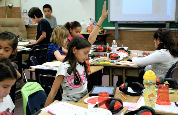 A student at Lumberg Elementary School in Edgewater raises her hand for assistance while students work on their iPads. (Nicholas Garcia/Chalkbeat)
