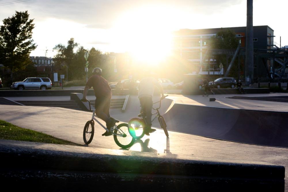BMX riders take in the sunset at the Denver Skate Park. (Andrew Kenney/Denverite)