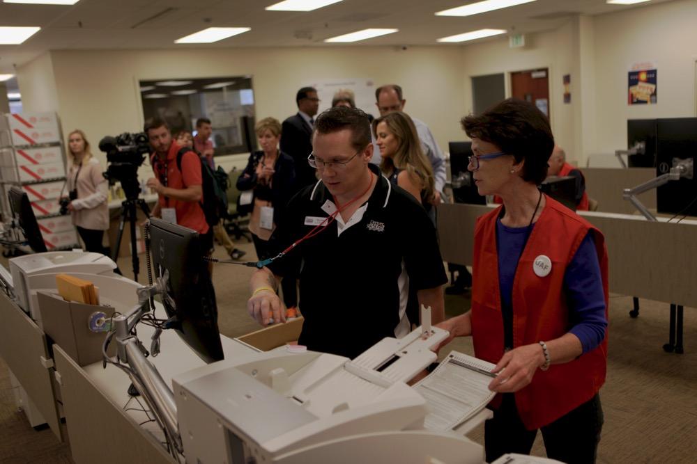Loading ballots for scanning. (Andrew Kenney/Denverite)