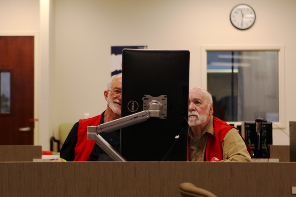 Richard Rew and Nathan Frazier, a bipartisan pair of election judges, review unclear ballot markings. (Andrew Kenney/Denverite)