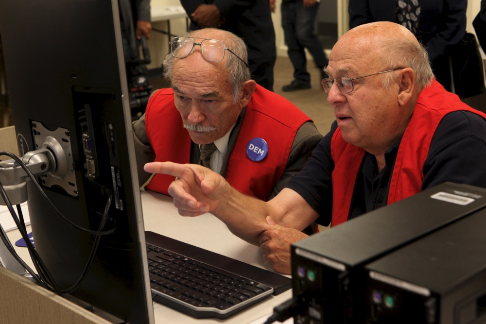 Bob Bair and David Bailey, a bipartisan pair of election judges, review unclear ballot markings. (Andrew Kenney/Denverite)