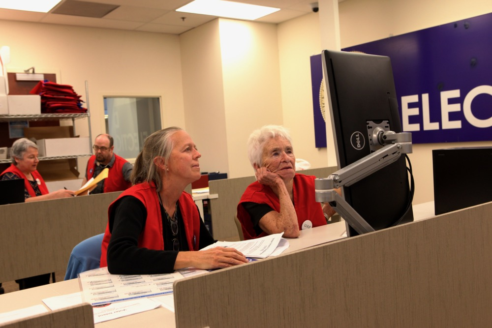 Rita Cawlfield and Charlotte Aycrigg review ballots in Denver. (Andrew Kenney/Denverite)