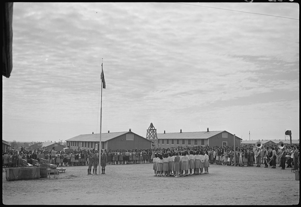 The U.S. flag is raised at a high school ceremony in the Granada Relocation Center, a concentration camp for people of Japanese descent, in Amache, Colorado. (Joe McClelland/National Archives and REcords Administration)