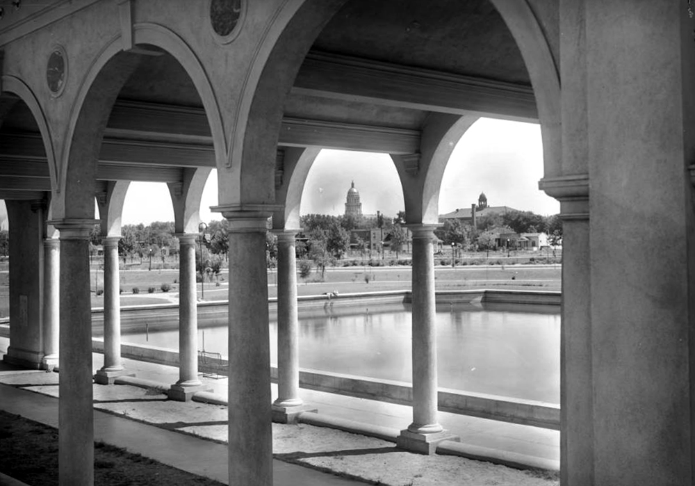 View toward Denver skyline from inside pavilion's archways, Sunken Gardens, near Speer Boulevard, Denver, Colorado, with raised pond or lake with cement walls; skyline includes Evans School at Eleventh (11th) and Acoma, Colorado State Capitol with gold dome and rotunda, and residences fronting park. Between 1911 and 1920. (Louis Charles McClure/Denver Public Library/Western History Collection/MCC-1944)  historic; denver public library; dpl; archive; archival; denverite