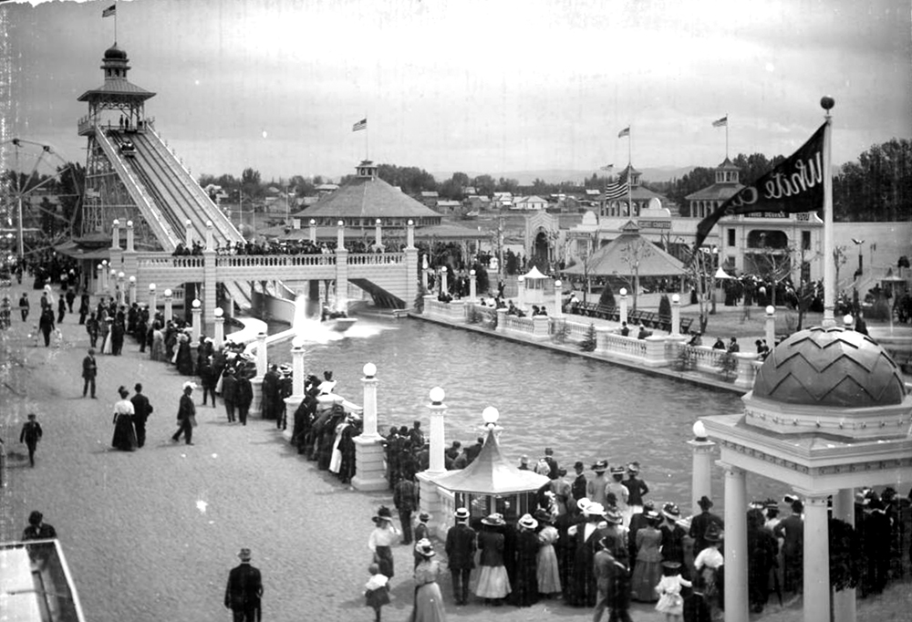 "View of ride called the Chutes (or the Big Splash), ""White City"" (later called Lakeside Amusement Park), Lakeside, Colorado, near Denver; shows a large crowd of people gathered and watching water ride, edge of ferris wheel, other rides, a penny arcade, a large line by ticket gazebo, and wooden frame residences behind boundary of amusement park. Between 1908 and 1910. (Louis Charles McClure/Denver Public Library/Western History Collection/MCC-943)  historic; denver public library; dpl; archive; archival; denverite"