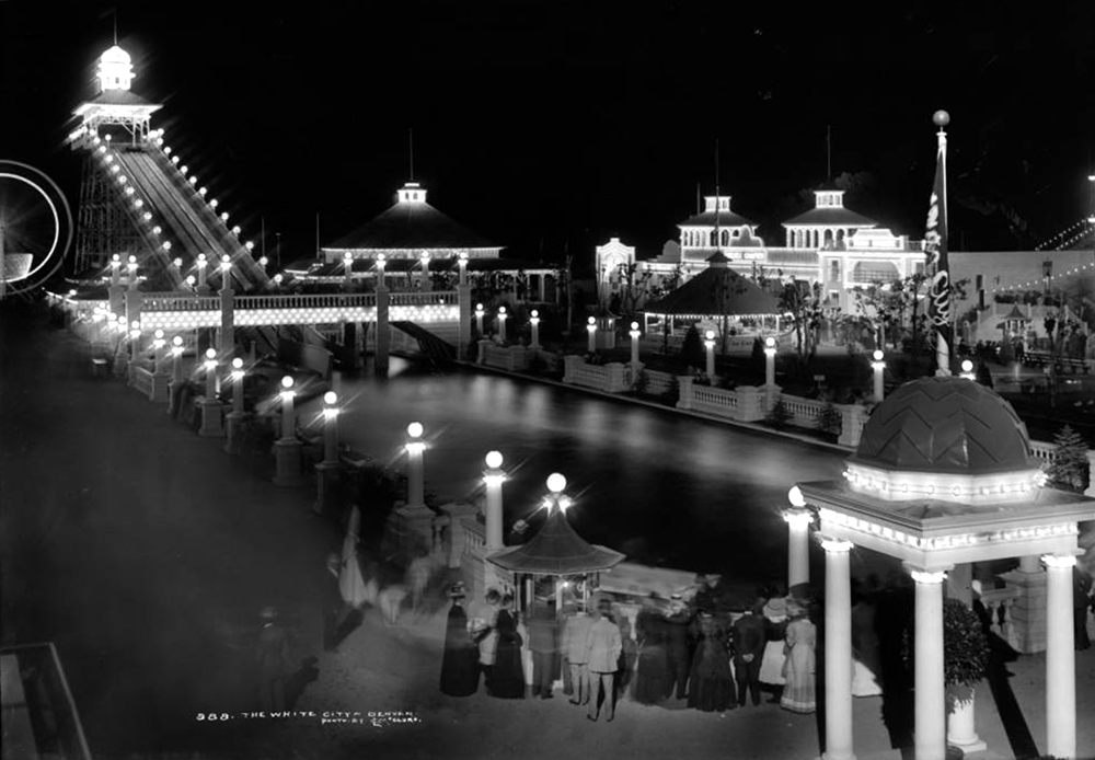 The White City, later called Lakeside Amusement Park, during a summer evening, Lakeside, Colorado near Denver; night time view of amusement park area with illuminated rides, sidewalks and buildings, people at ticket gazebo, the Big Splash, Casino Theater and Cafe. Between 1908 and 1910. (Louis Charles McClure/Denver Public Library/Western History Collection/MCC-888)  historic; denver public library; dpl; archive; archival; denverite