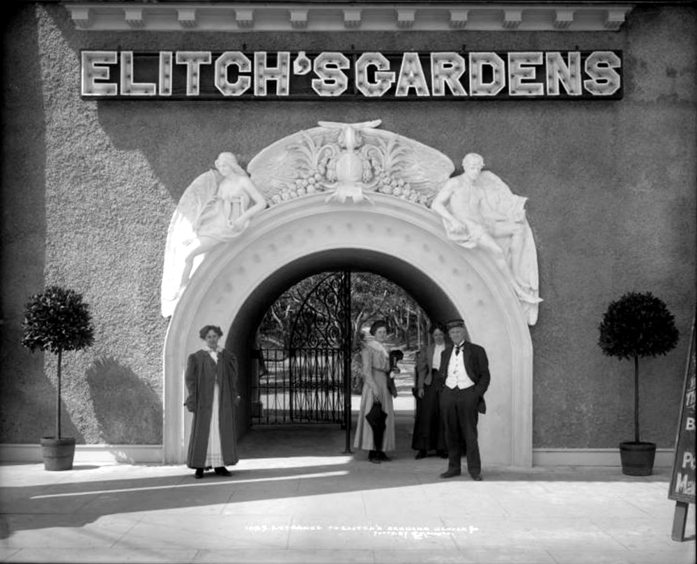 Close-up view of main entrance to Elitch's Gardens at West 38th (Thirty-eighth) Avenue and Tennyson Street, Denver, Colorado; artistic statues posed over entrance lead to wrought iron gate; three women and a male Elitch's employee stand in front of entrance. Circa 1910. (Louis Charles McClure/Denver Public Library/Western History Collection/MCC-1059)  historic; denver public library; dpl; archive; archival; denverite