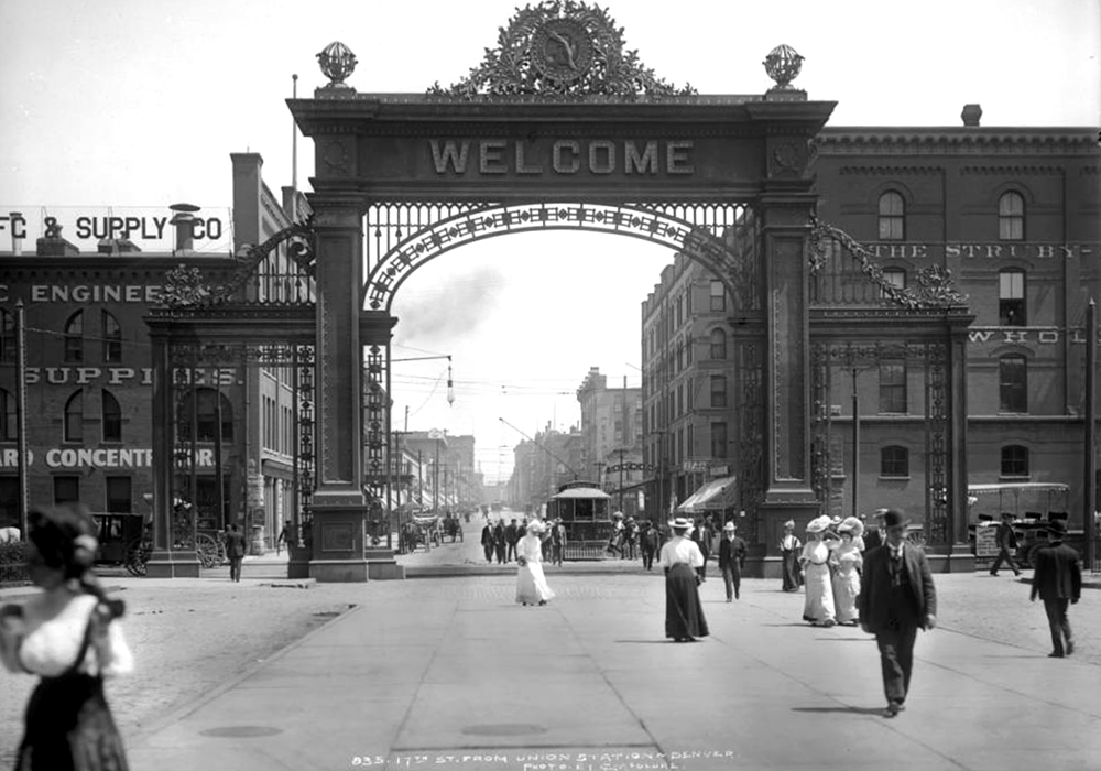 Welcome Arch at Union Station in Denver, Colorado; view of 17th (Seventeenth) street, street railway car number 248, men and women walking towards Union Station (not in view). Between 1906 and 1910. (Louis Charles McClure/Denver Public Library/Western History Collection/MCC-835)