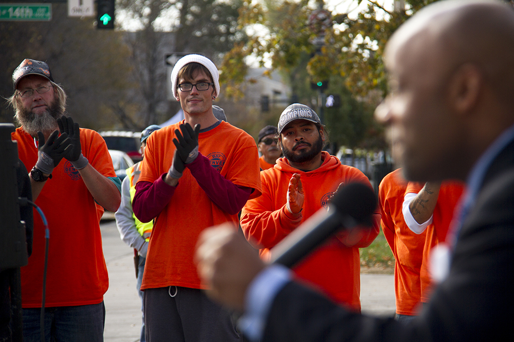 Jerry Haller (left to right), Derek Christianson and Refugio Ortiz clap during Mayor Michael Hancock's speech launching Denver Day Works. (Kevin J. Beaty/Denverite)  homeless; day labor; social work; kevinjbeaty; denverite; denver; colorado; kevinjbeaty;