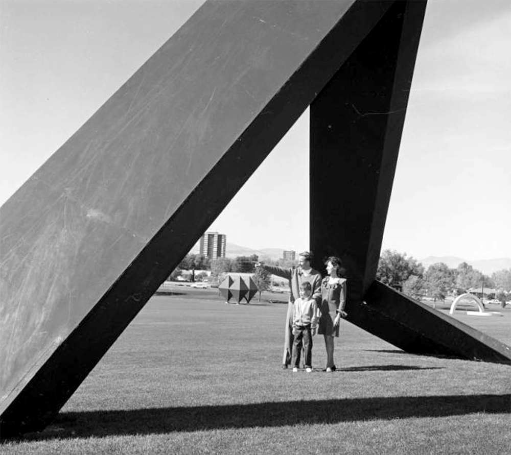 A man, woman and a young boy stand near a large, abstract, plywood sculpture by Anthony Mygar in Burns Park near the intersection of East Alameda Avenue and South Colorado Boulevard, in the Hilltop neighborhood, Denver, Colorado. Between 1968 and 1970. (Lloyd Rule/Denver Public Library/Western History Collection/Z-11801)  history colorado; historic; denver public library; dpl; archive; archival; denverite
