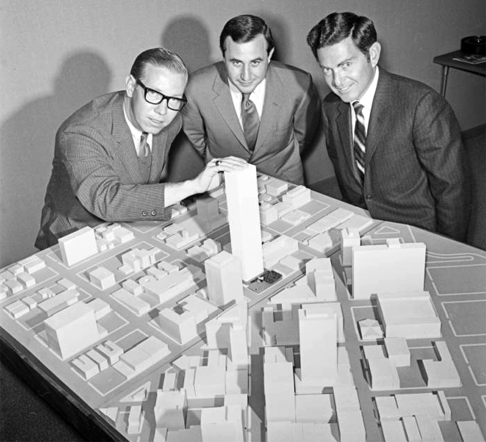 Three men look at a model of a proposed building in Denver, Colorado. The model encompasses several blocks of downtown Denver, one of the men has his hand on the top of the proposed building. Between 1970 and 1975. (Lloyd Rule/Denver Public Library/Western History Collection/Z-11880)  history colorado; historic; denver public library; dpl; archive; archival; denverite
