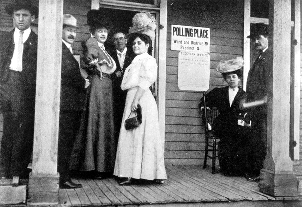 """Early women voters."" Well dressed men and women sit and stand on the porch of a building with signs that reads: ""Polling Place, Ward and District 9, Precinct 1"" and ""Election Notice."" (Denver Public Library/Western History Collection/Z-8811)  election; voting; suffrage; history colorado; historic; denver public library; dpl; archive; archival; denverite"