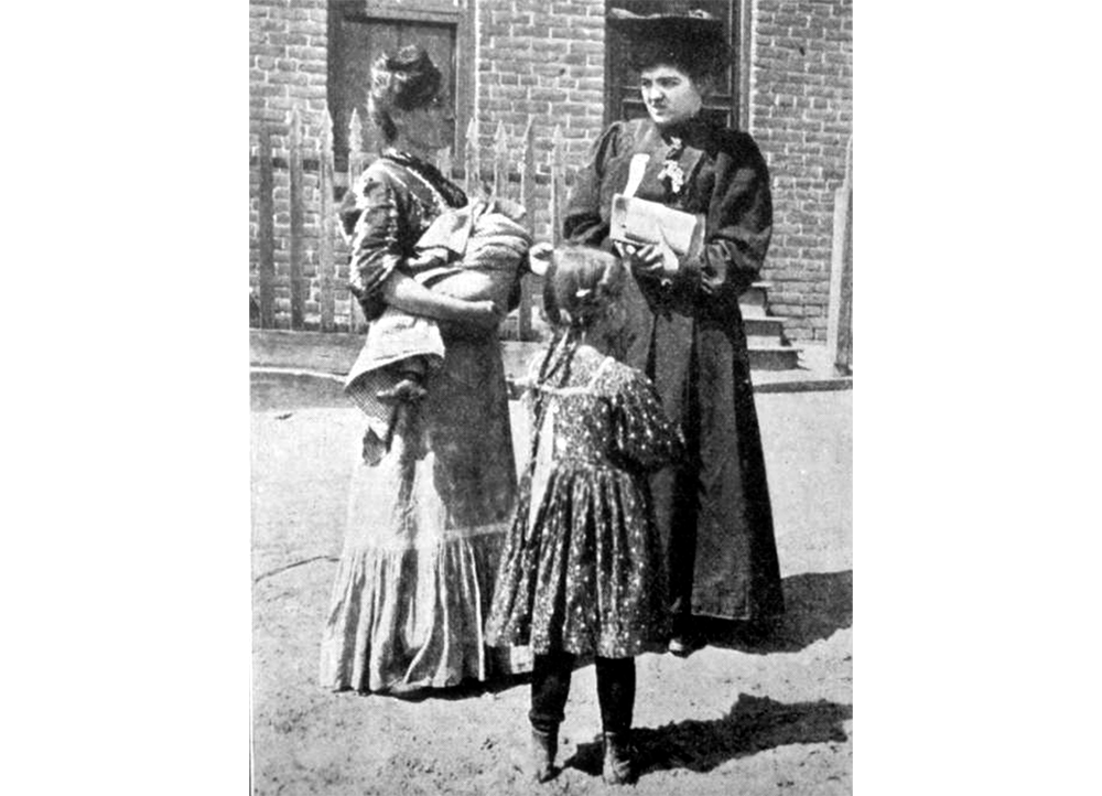 """""""Early women voters."""" View of a woman, a ward worker, in a dark dress and hat, talking to a woman who holds a baby and stands with a young girl. (Denver Public Library/Western History Collection/Z-8811)  election; voting; suffrage; history colorado; historic; denver public library; dpl; archive; archival; denverite"""