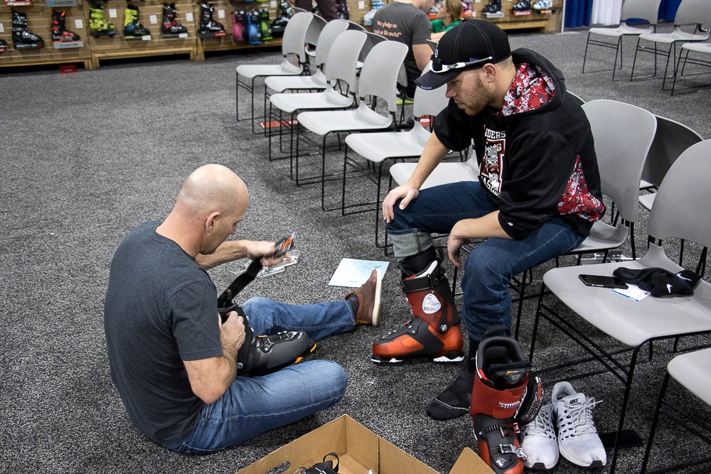 Rob McGregor helps Daniel Solomon try on boots at the Ski and Snowboard Expo.(Chloe Aiello/Denverite)