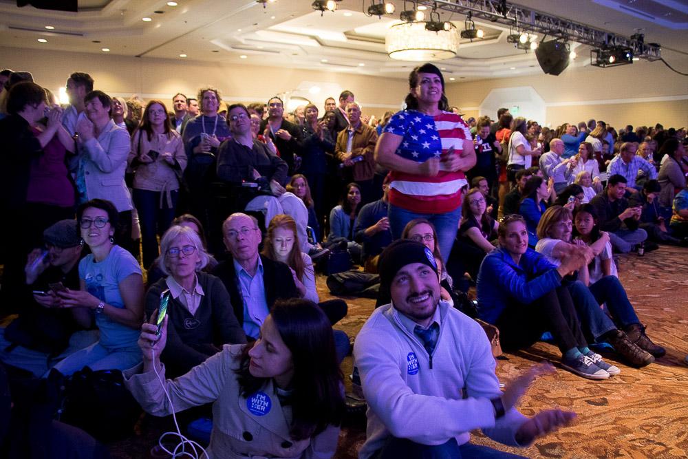 Pamela Medina, John Rose and  Ronnie Rodriguez celebrate the moment Hillary Clinton won Colorado. (Chloe Aiello/Denverite)