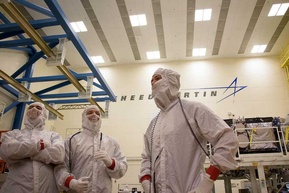 Taylor Fleury, Nick Flannigan and Derek Sweatt pose in front of the GOES-S weather satellite. (Chloe Aiello/Denverite)