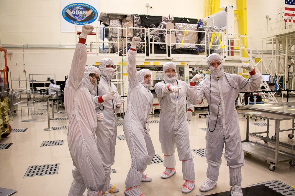 Taylor Fleury, Nick Flannigan and Derek Sweatt pose in front of the GOES-S weather satellite. (Chloe Aiello/Denverite)