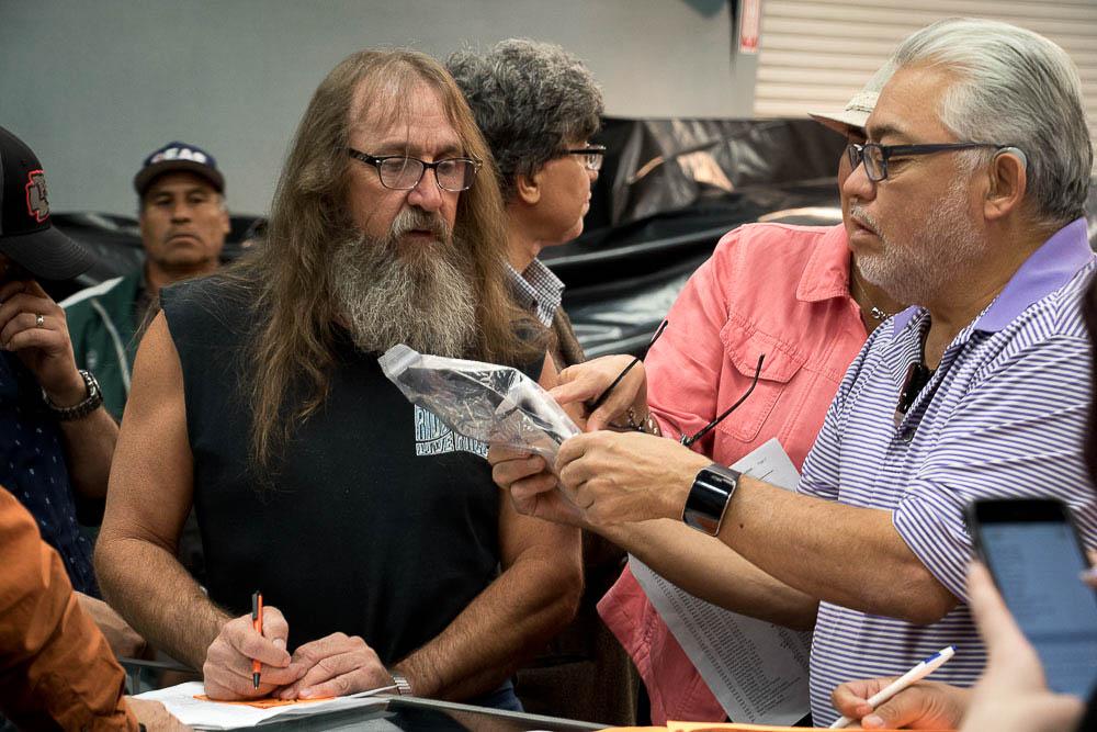 Men examine jewelry at the city of Denver's auction. (Chloe Aiello/Denverite)