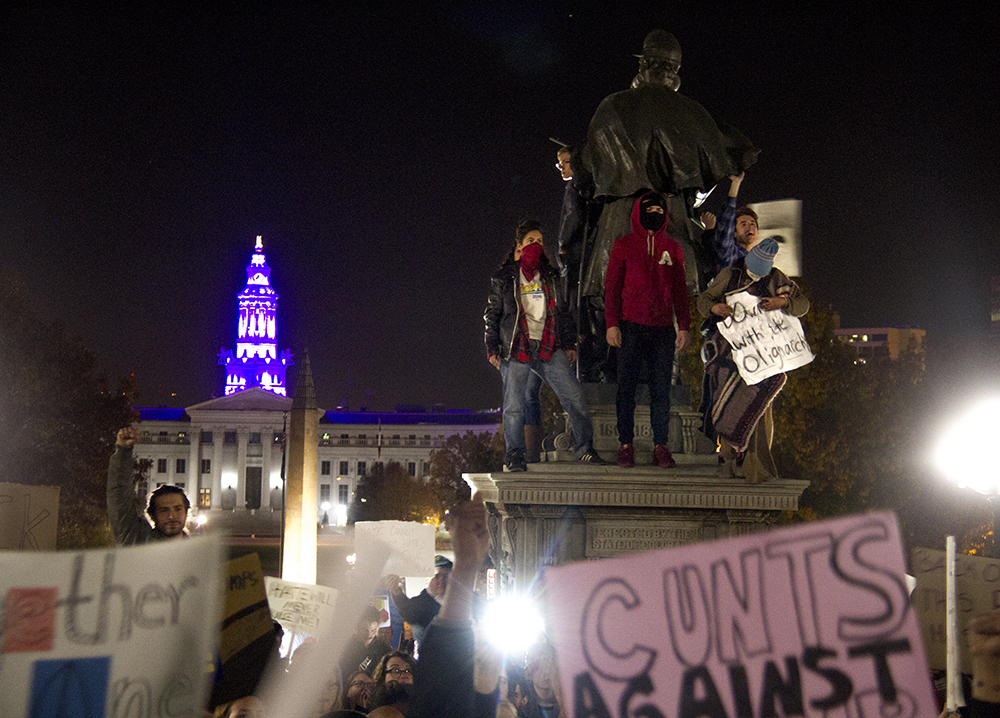 Protesters stand atop a statue in front of the Capitol. An anti-Trump rally. Nov. 11, 2016. (Kevin J. Beaty/Denverite)  politics; protest; denver; denverite; kevinjbeaty; colorado; trump;