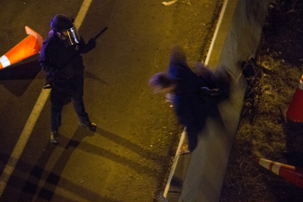 An officer with a baton allows someone to jump a concrete barrier beside I-25 and leave. An anti-Trump rally. Nov. 11, 2016. (Kevin J. Beaty/Denverite)  politics; protest; denver; denverite; kevinjbeaty; colorado; trump;