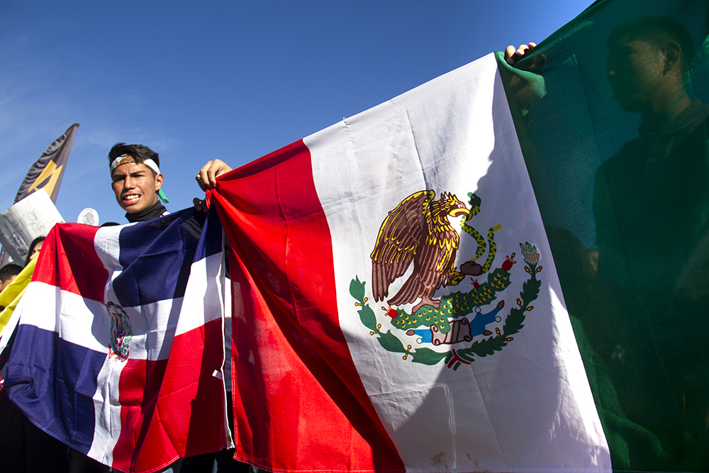 Kevin Garcia holds a flag during a rally held by high school students in Ruby Hill after a multi-school walk-out. (Kevin J. Beaty/Denverite)  protest; rally; march; students; ruby hill; trump; politics; election; kevinjbeaty; copolitics; denver; denverite; colorado; latino; hispanic;