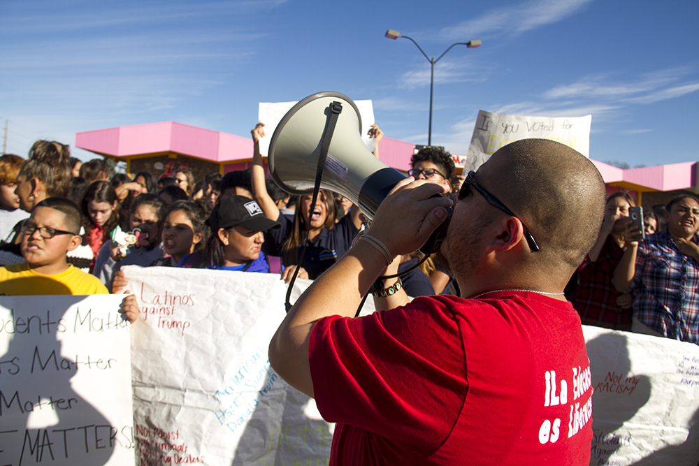 Padres and Jovenes Unidos youth leader Juan Evangelista leads chants at the front of a rally held by high school students in Ruby Hill after a multi-school walk-out. (Kevin J. Beaty/Denverite)
