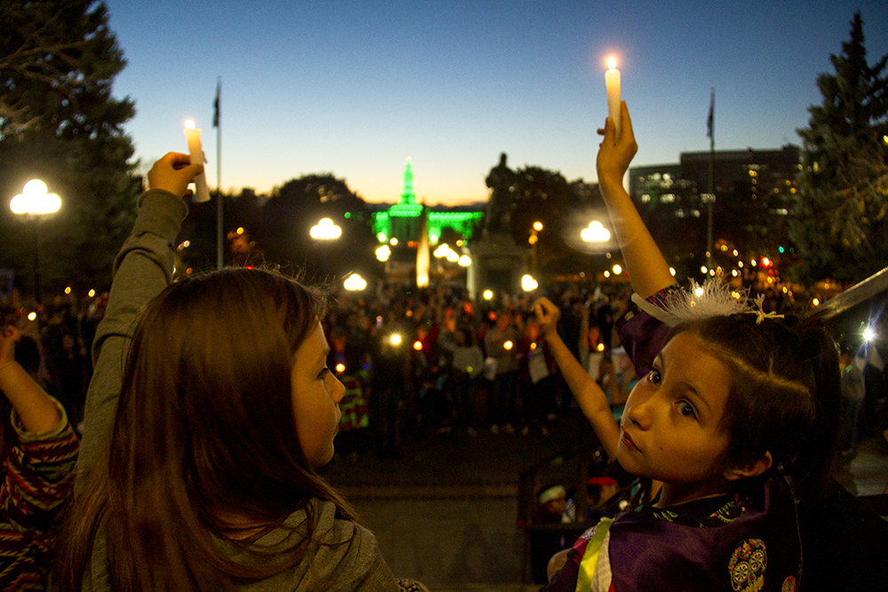 Lucille Left Hand Bull (right) holds a candle in the air during a rally in solidarity with protesors at Standing Rock, North Dakota.(Kevin J. Beaty/Denverite)  standing rock; protest; rally; capitol hill; denverite; denver; colorado; kevinjbeaty;