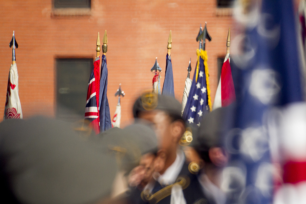 Flags above JROTC students standing in formation before the Veterans Day parade at Civic Center Park. Nov. 12, 2016. (Kevin J. Beaty/Denverite)