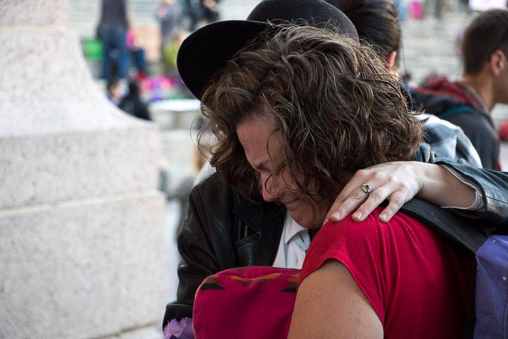 Rebecca Carpenter, 33, hugs a stranger in Civic Center Park to support Community for Unity after Thursday's march. (Chloe Aiello/Denverite)