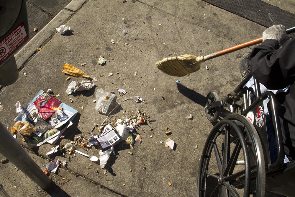 """JR Gerhard sweeps up garbage. """"Homeless sweeps"""" on Nov. 15, 2016. (Kevin J. Beaty/Denverite)homeless; sweeps; denver rescue mission; police; justice; kevinjbeaty; denver; denverite; colorado; camping ban; right to rest;"""