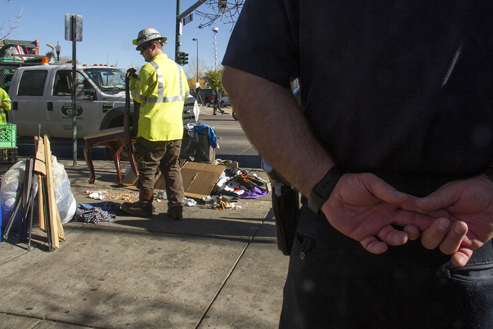 "City workers sort garbage from personal items, loading the former into a garbage truck and the latter into garbage bins for 30-day storage. ""Homeless sweeps"" on Nov. 15, 2016. (Kevin J. Beaty/Denverite)homeless; sweeps; denver rescue mission; police; justice; kevinjbeaty; denver; denverite; colorado; camping ban; right to rest;"
