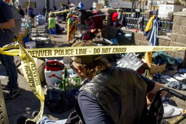 "JR Gerhard ducks under caution tape to collect his belongings. ""Homeless sweeps"" on Nov. 15, 2016. (Kevin J. Beaty/Denverite)homeless; sweeps; denver rescue mission; police; justice; kevinjbeaty; denver; denverite; colorado; camping ban; right to rest;"
