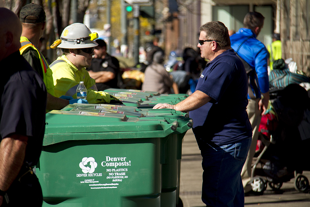 """City workers load bins with personal items for 30-day storage. """"Homeless sweeps"""" on Nov. 15, 2016. (Kevin J. Beaty/Denverite)"""