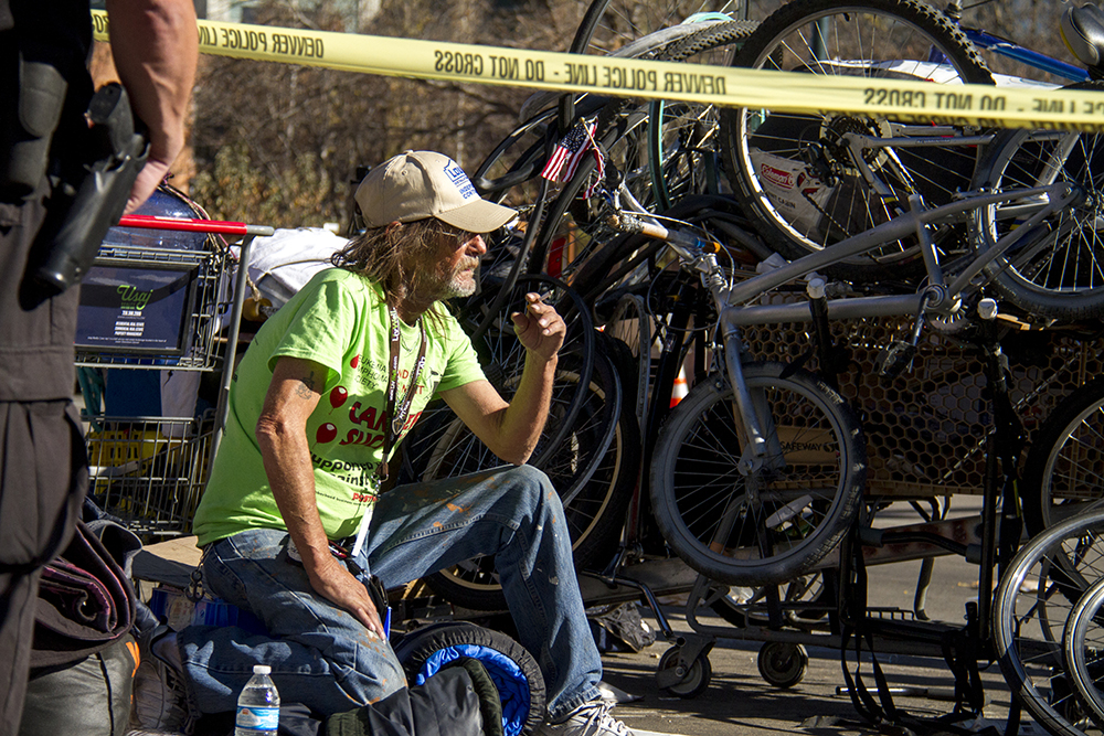 """Randy Russell sits beyond a police line. """"Homeless sweeps"""" on Nov. 15, 2016. (Kevin J. Beaty/Denverite)homeless; sweeps; denver rescue mission; police; justice; kevinjbeaty; denver; denverite; colorado; camping ban; right to rest;"""