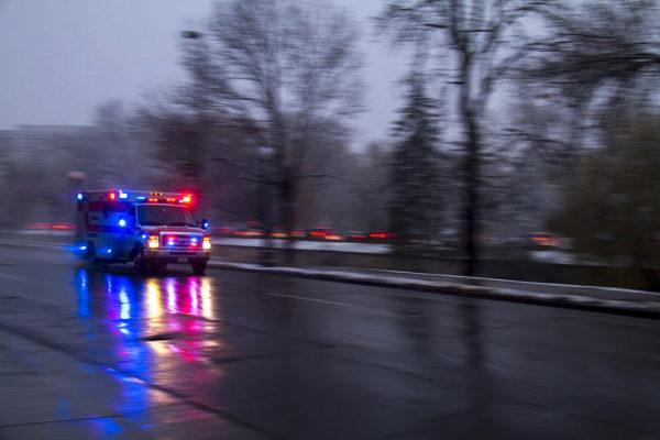 An ambulance screams down Speer on a snowy evening. Nov. 17, 2016. (Kevin J. Beaty/Denverite)  snow; cowx; weather; denver; winter; snow; kevinjbeaty; colorado; denverite;