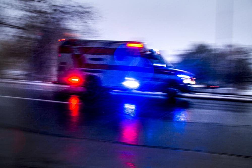 An ambulance screams down Speer on a snowy evening wiht its sirens on. Nov. 17, 2016. (Kevin J. Beaty/Denverite)
