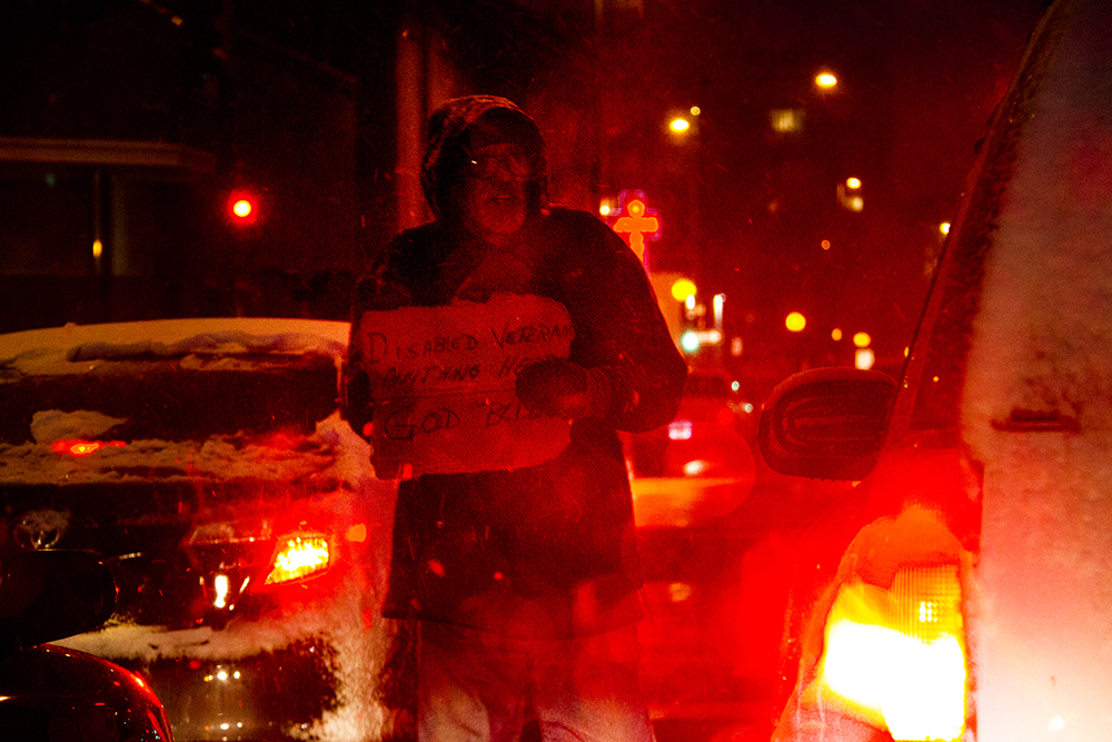 A man asks for money on Park on a blizzardous evening. Nov. 17, 2016. (Kevin J. Beaty/Denverite)  snow; cowx; weather; denver; winter; snow; kevinjbeaty; colorado; denverite; homeless; park avenue;