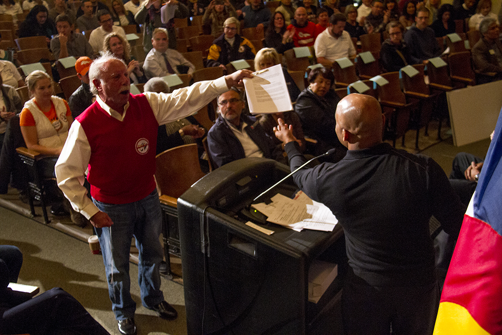 Louis Plachowski interrupts Mayor Michael Hancock's Cabinet in the Community event as he hands a petition against the City Park Golf Course drainage plan. Nov. 19, 2016. (Kevin J. Beaty/Denverite)  mayor michael hancock; cole arts and science academy; politics; government; ditch the ditch; protest; kevinjbeaty; denver; denverite; colorado;