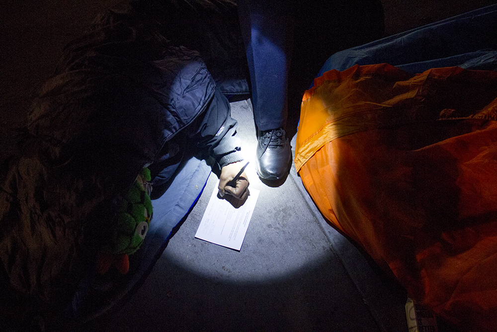 """A man who goes by """"Possum"""" signs a written warning to vacate. Protesters who have set up camp in front of the City and County Building to denounce Denver's urban camping ban are removed by police. Nov. 29, 2016. (Kevin J. Beaty/Denverite)  camping ban; right to rest; homeless sweeps; city and county building; police; protest; kevinjbeaty; denver; denverite; colorado;"""