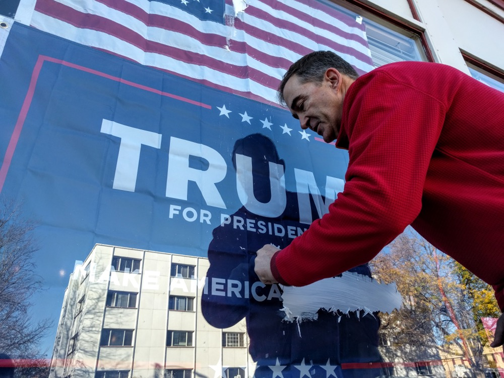 Jeffrey Eggemeyer cleans graffiti from a window at Trump's Denver office. (Kevin J. Beaty/Denverite)