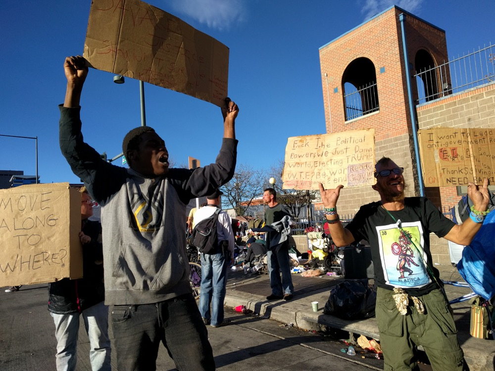 King Reality and Lindsay Leporis protest expected sweeps of homeless people in the Ballpark neighborhood. (Kevin J. Beaty/Denverite) camping ban; right to rest; homeless;