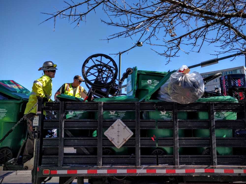 A truck collects belongings of homeless people who had camped on the sidewalk of Park Avenue West and Broadway. (Kevin J. Beaty/Denverite) camping ban; right to rest; homeless