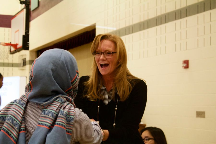 Rebecca McClellan, a candidate for the State Board of Education, greets a participant at a forum in Aurora. (Nicholas Garcia/Chalkbeat)