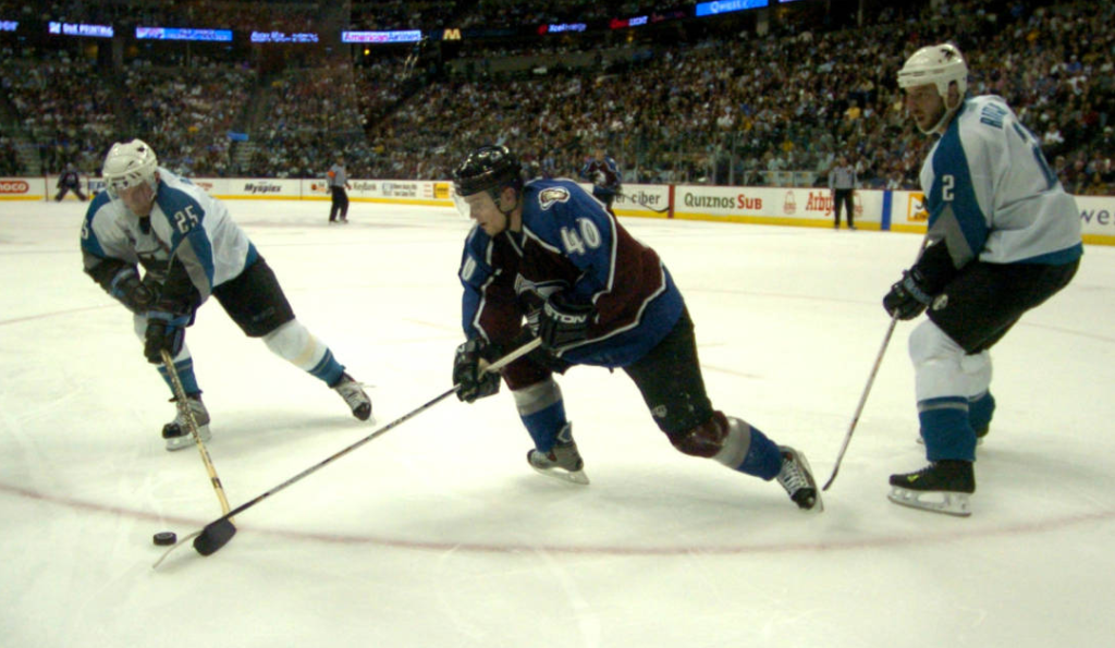 Colorado Avalanche Marek Svatos, #40, tries to keep the puck in the visitor's zone against San Jose Sharks Vincent Bamphousse, #25, and Mike Rathje, #2, in the third period of the Shark's 1-0 victory in Game 3 of their Western Conference semifinal playoff series in the NHL's 2004 Stanley Cup Playoffs in Denver at the Pepsi Center on April 26, 2004. (Denver Public Library/Joe Mahoney/Rocky Mountain News/RMN-020-4206 )