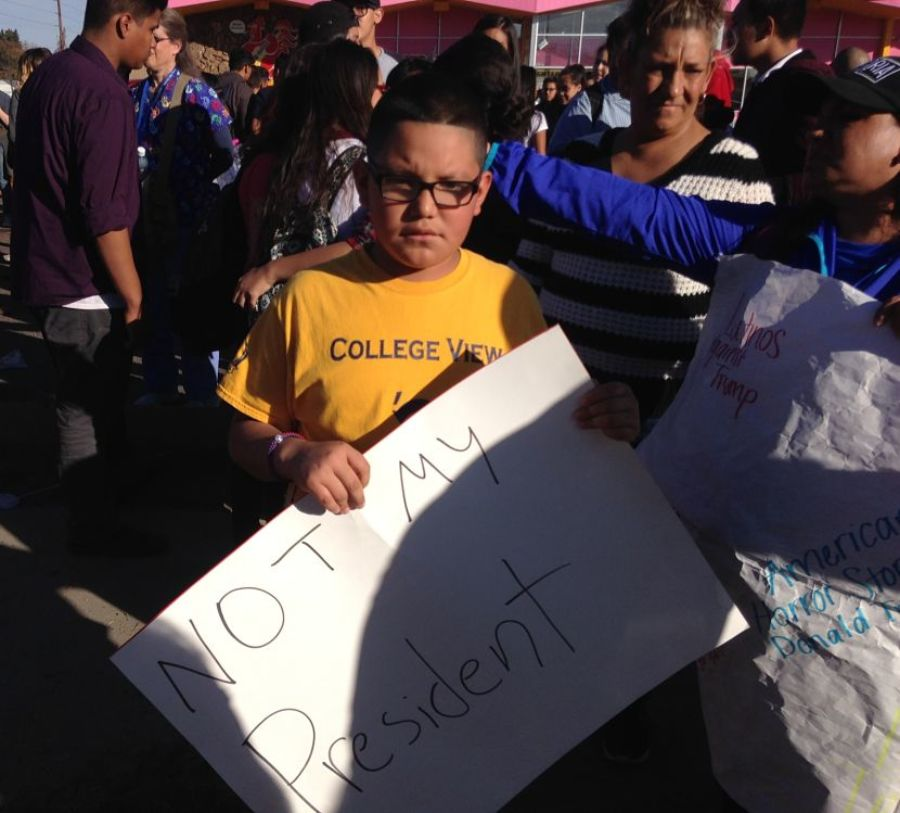 A Denver student holds a sign at a walkout to protest Trump. (Melanie Asmar/Chalkbeat)